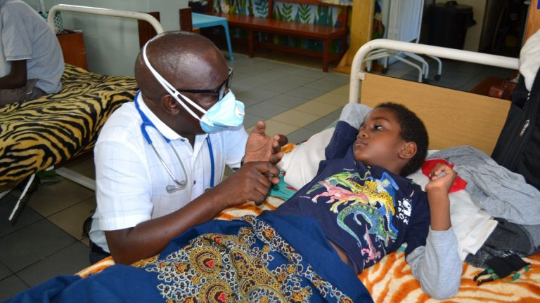 Dr George Paediatric Oncologist in Malawi with patient World Child Cancer